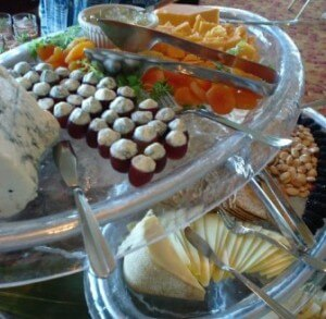 A close-up of a cheese bar with different types of cheeses, cheese knife, fork and apricots.