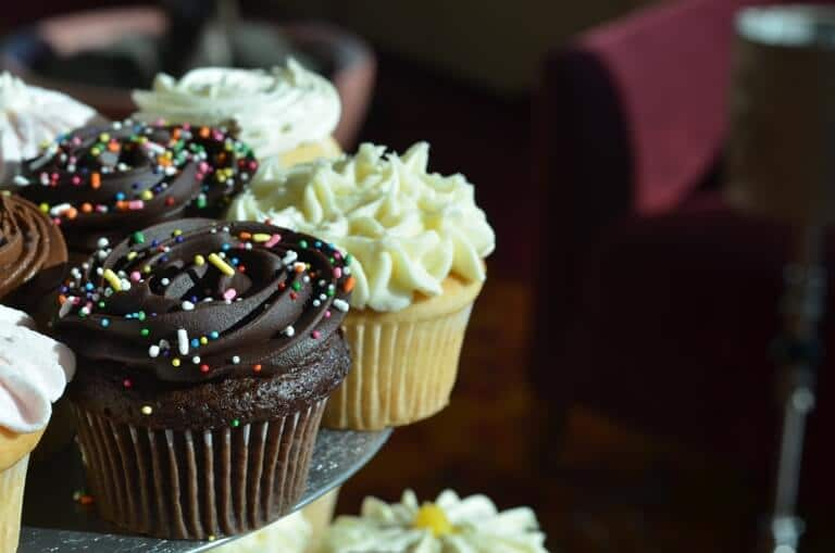 A close-up of different colored cupcakes with sprinkles on a table, a red chair in the background
