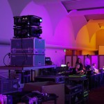 Technical equipment, staff working in the background in a colorful purple-lighted room