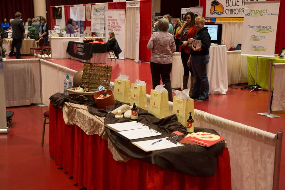 A booth at a trade fair event with sample lotion bottles, paper bags and forms on it with people in the background