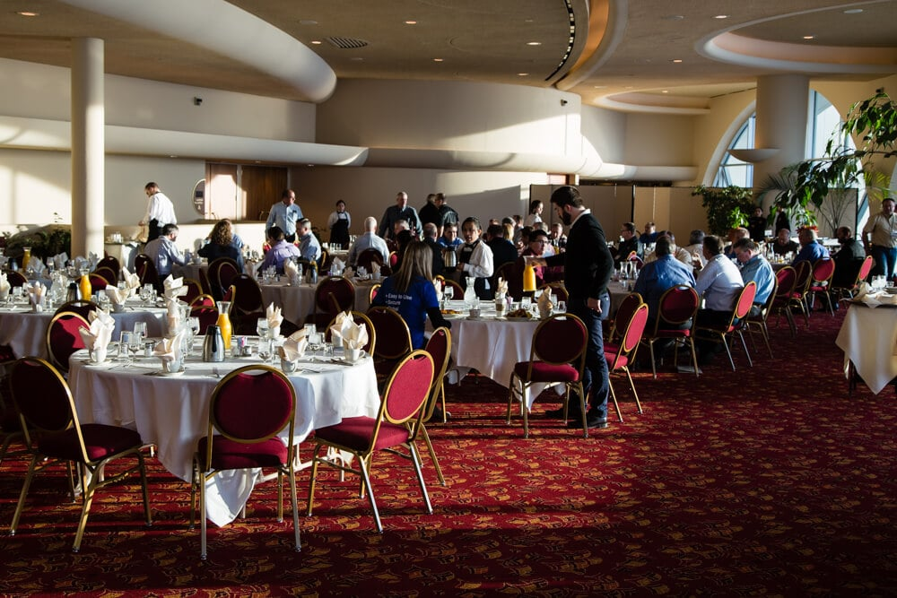 People gathered around round tables having breakfast at an event