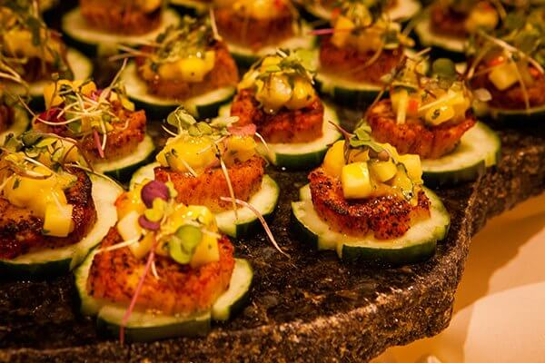 Close-up of a plate of canapes with seared scallops on cucumber slices and mango salsa on top