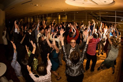 A group of people are dancing in formal outfits, their hands are up in the air in a venue