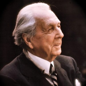 A picture of Frank Lloyd Wright smiling in a suit and tie