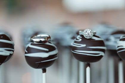 A close-up photo of chocolate cake pops with engagement rings on top of them.