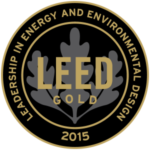 A circle gold plaque logo for Leed Gold Leadership in Energy and Environmental Design 2015, with a leaf visible in black background