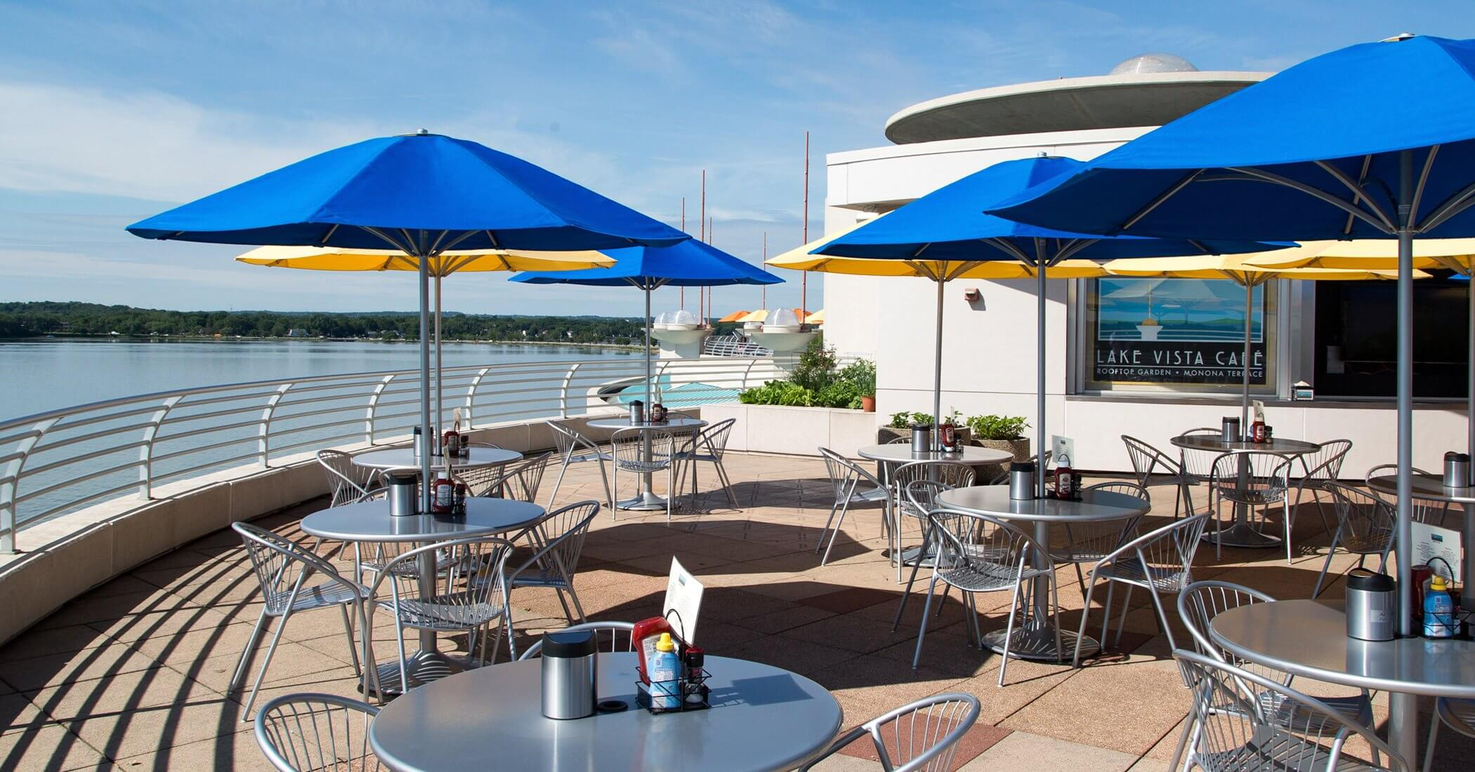 Empty tables at Lake Vista Cafe with a view of the lake with yellow and blue umbrella canopies