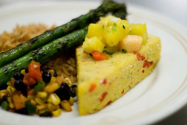 Close-up of a dish with polenta, corn salsa, brown rice and two pieces of asparagus