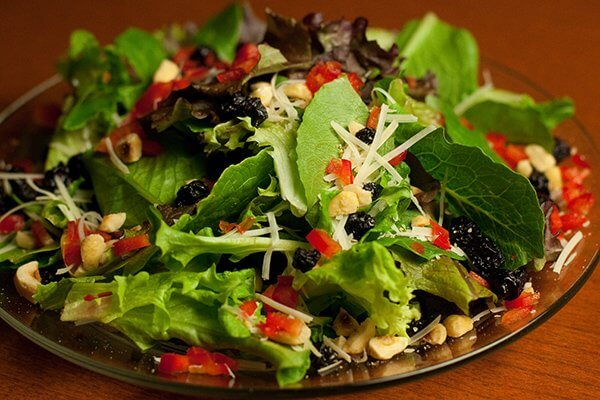 Close-up of a salad course with mixed greens, cashew nuts and red peppers, as well as shredded parmesan