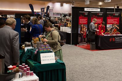A trade fair event, booths with products on top, people investigating the products.