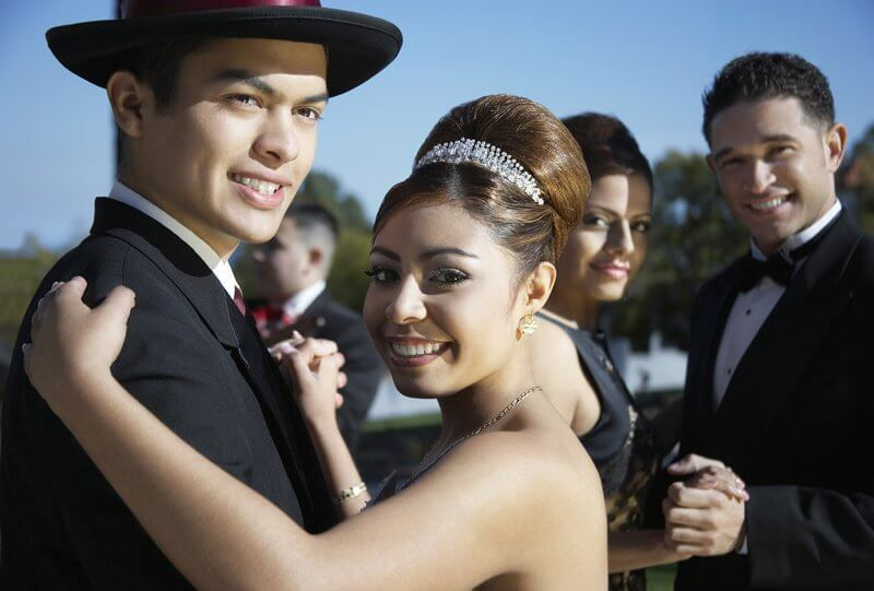 Two Latin American couples in formal outfits posing for camera, dancing and celebrating Quinceanera, a guy in the background
