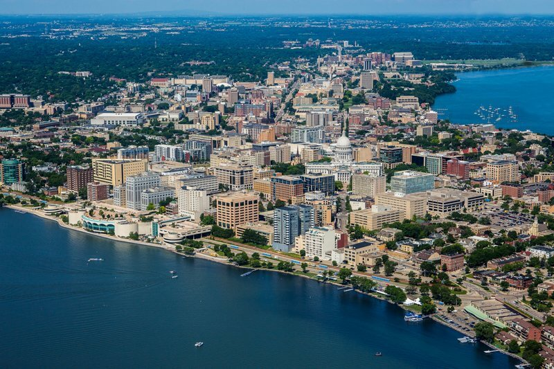 Aerial view of Madison with Lake Monona, city buildings stacked together and Monona Terrace standing out on the lakeshore