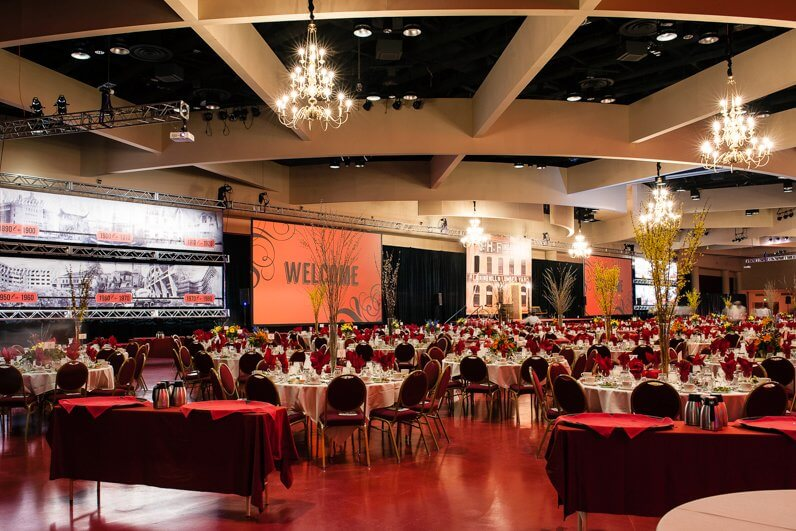 Monona Terrace large event room with round tables, coffee stations and big presentation screens