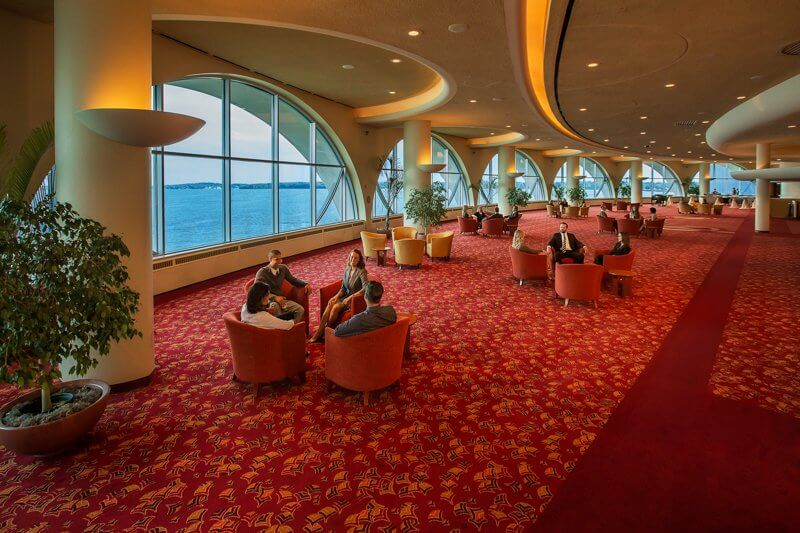 Monona Terrace spacious lounge with views of the lake and different groups of people sitting in different areas of the lounge
