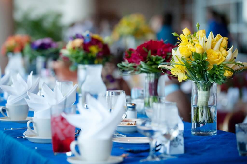 A close-up a party table with glasses and folded napkins on it, yellow and pink flowers in orderly placed vases