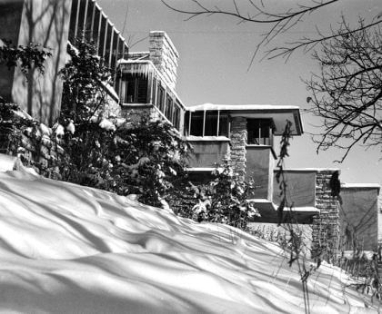 A black-and-white photograph by Guerrero of a view of a house covered in snow with trees from a lower angle.