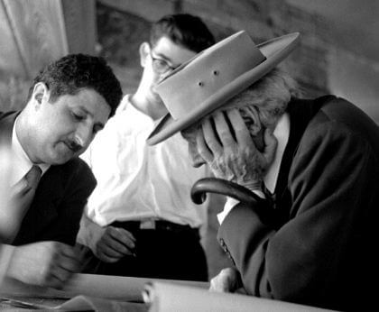 An old black-and-white photo of Frank Llyod Wright with a hat, looking at design sketches with Pedro E. Guerrero