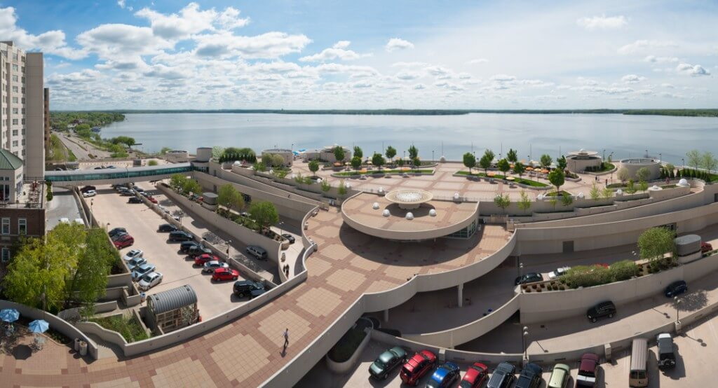A panoramic view of William T. Evjue Rooftop Gardens by the lake with trees, and cars parked on lower levels of the building