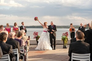 A wedding photo of a couple getting married at Monona Terrace in front of their guests