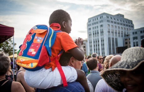 little boy with a backpack in a crowd