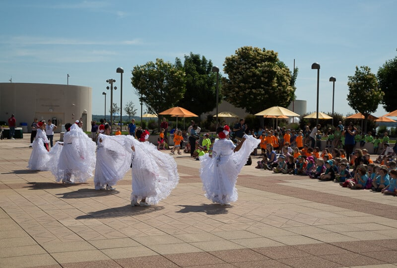 group of people dancing in white costumes