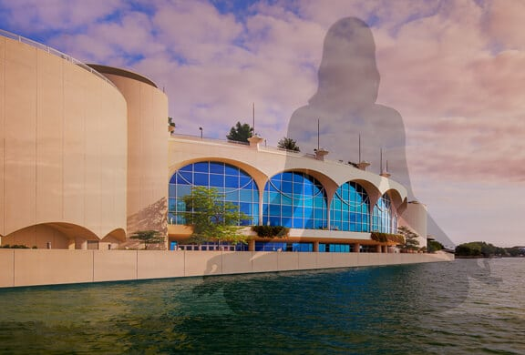 View of Monona Terrace from the lake with a faded silhouette of a woman in meditation pose