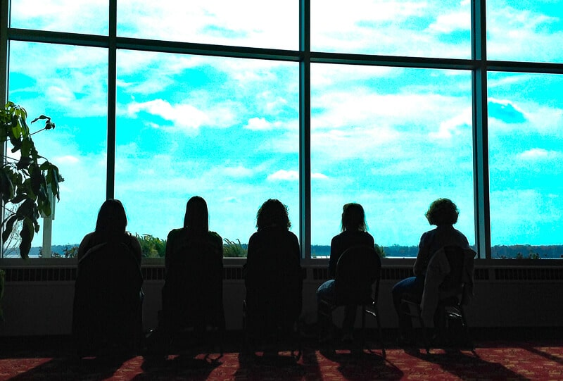 group of people sitting next to a window