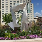 close up of a flower garden and a sculpture in front of a building