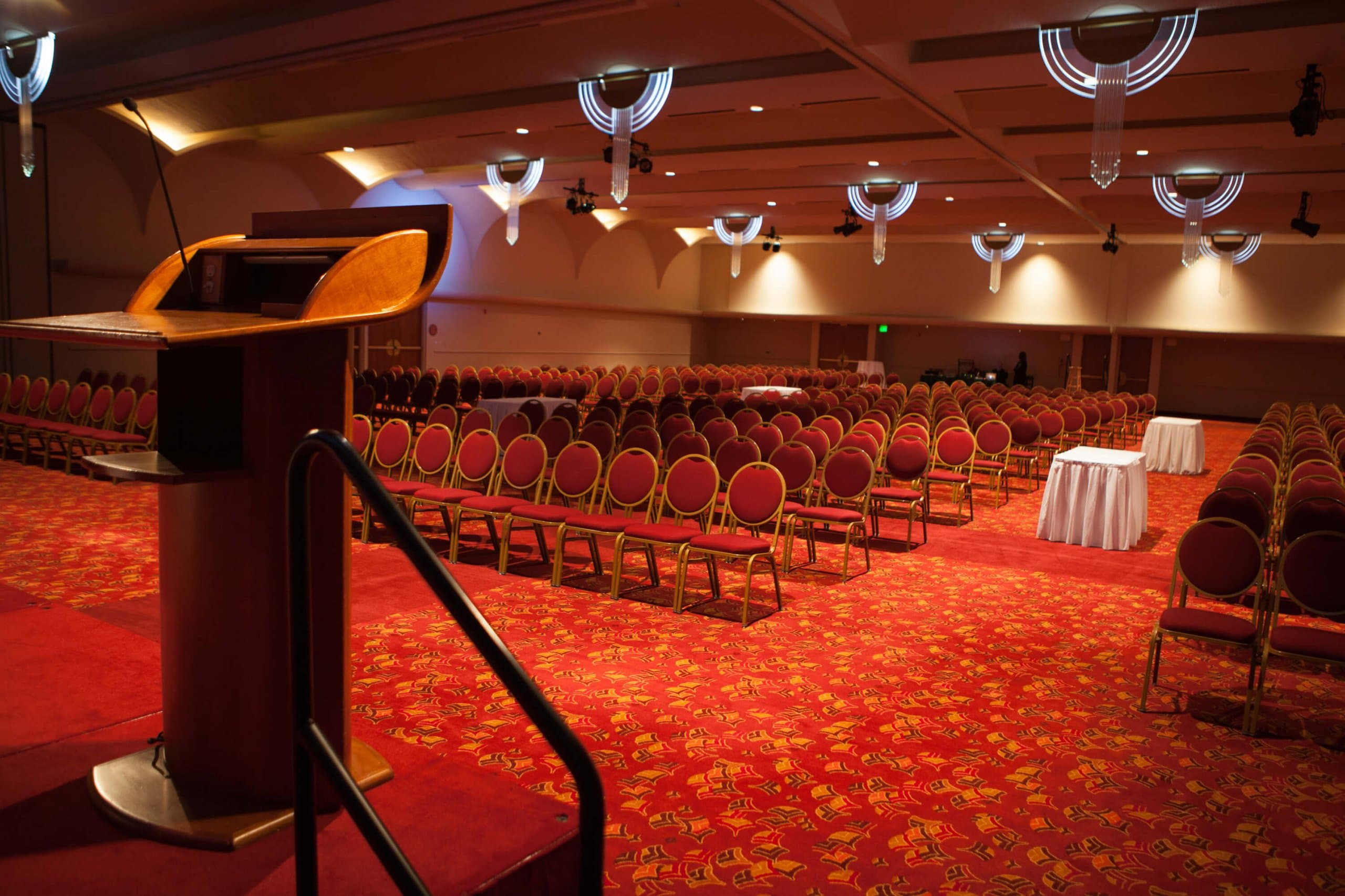 An empty conference hall with red carpet, red chairs, two tables with white tableclothes and a podium on the stage.