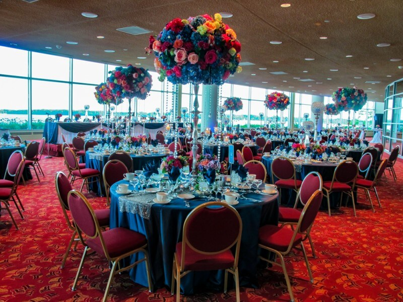 A wedding hall with decorated round tables, with a glittering flower decoration on candle sticks as the centerpieces on every table.