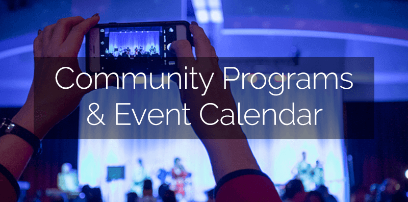 "A photo of hands taking a photo of the stage during an event, with ""Community Programs & Event Calendar"" written on it."