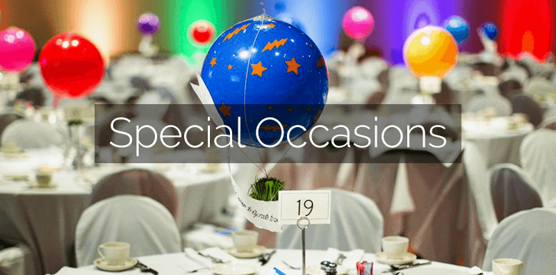 """A close-up of party tables with colorful balloons. """"Special Occasions"""" is written on the picture."""