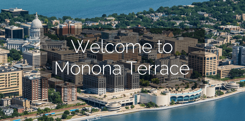 "Aerial view of Monona Terrace with Lake Monona and city buildings with ""Welcome To Monona Terrace"" written"