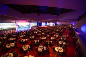Large event room with round tables and big presentation screens from a distance