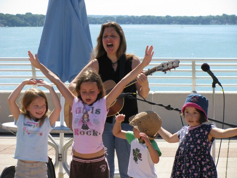 little girls singing and dancing next to a body of water
