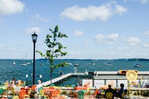 People sitting at the Memorial Union Terrace, looking at boats on Lake Mendota on yellow, orange and green chairs