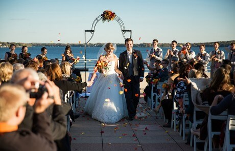 A newlywed couple walking down the aisle by the lake, as guests throw rose petals and applaud