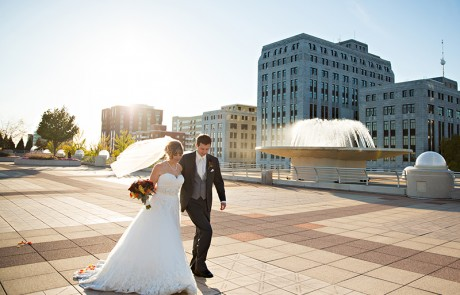 A newlywed couple walking together outside of Monona Terrace, buildings and a big ornamental pool in the background