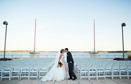 Bride and groom kissing by the lake, empty chairs and tall lamps in the background