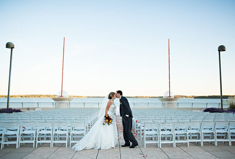 Bride and groom kissing by the lake, empty chairs in the background