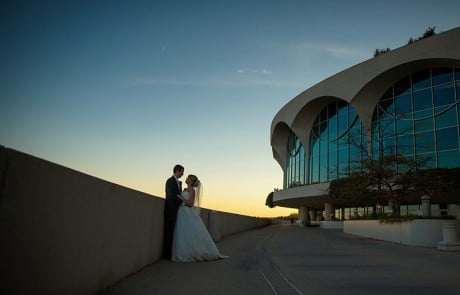 Bride and groom looking at each other, posing from a distance next to the side of Monona Terrace building by a concrete wall
