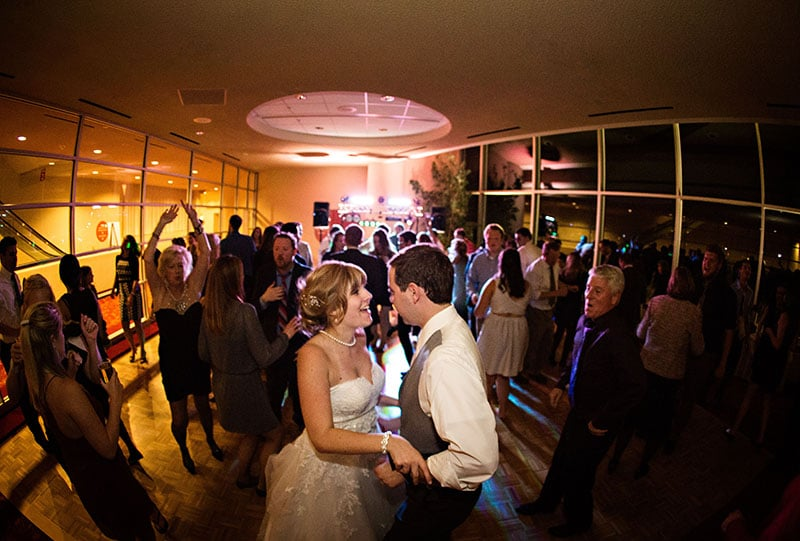 A newlywed couple and guests dancing in a venue