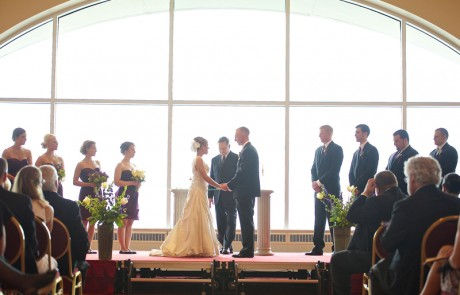 A couple getting married in front of a wedding altar, bridesmaids and groomsmen standing, as guests watch.