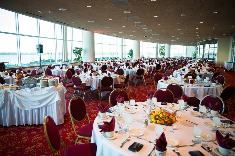 Decorated round tables at an empty wedding dining hall by big windows with a distant lake view