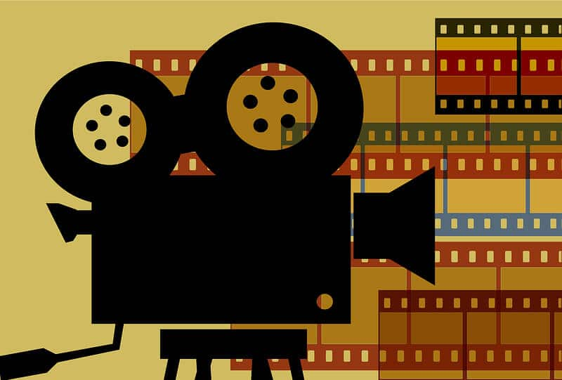 A black sketch of an old school movie camera on a stand with reels on top and a yellow background with colored film rolls