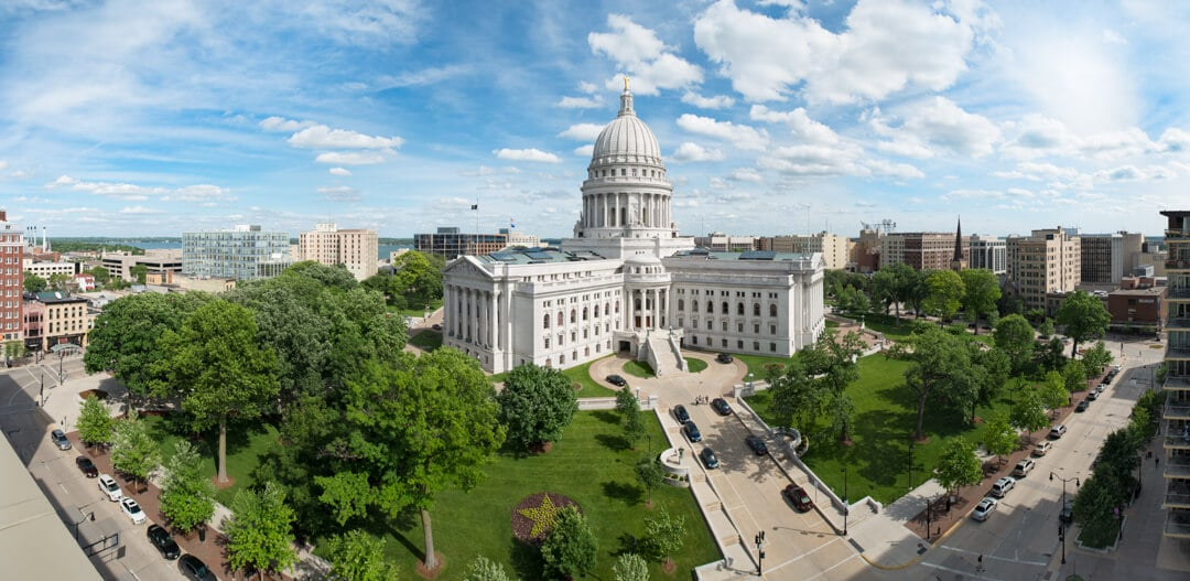 The Wisconsin State Capitol building among trees in daytime, city buildings in the background with a distant view of the lake.