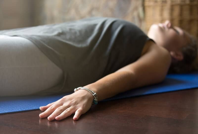 woman laying down on yoga mat relieving stress of the day