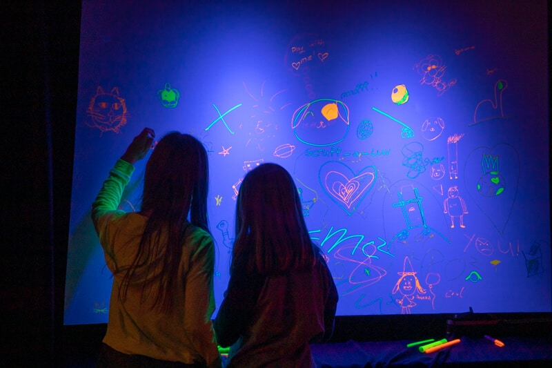2 children write on a whiteboard with glow-in-the dark pens