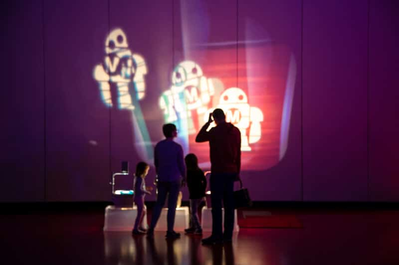 A robot is projected onto a wall in various overlapping colors a family is in shadow in the foreground