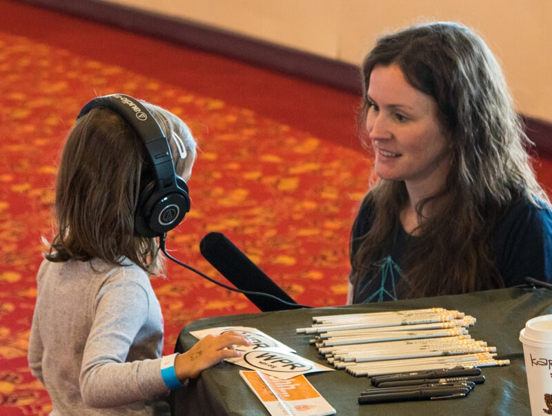 Wisconsin Public Radio Announcer demonstrates headphones to a young listener
